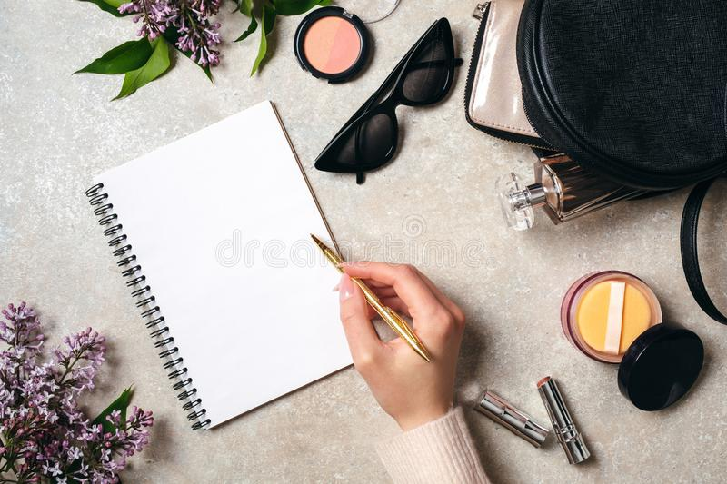 Top view hand of woman writing text message on blank paper notebook on stone table. Flat lay lilac flower, feminine cosmetic, royalty free stock photo