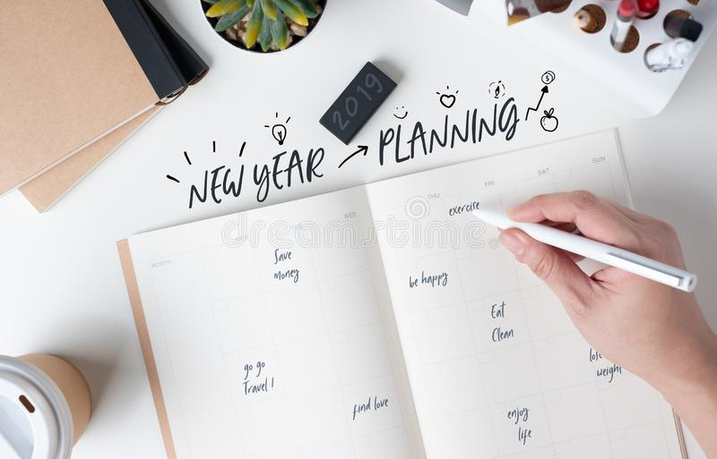 Top view of hand writing new year`s planning on open calendar planner with doodle style for life resolution with modern office royalty free stock photos