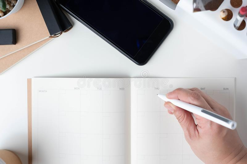 Top view of hand writing on open calendar planner for business resolution with modern office stationery and take away coffee cup royalty free stock image