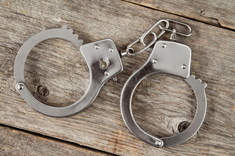 Top view of handcuffs. Top view of handcuffs on the wooden background stock images