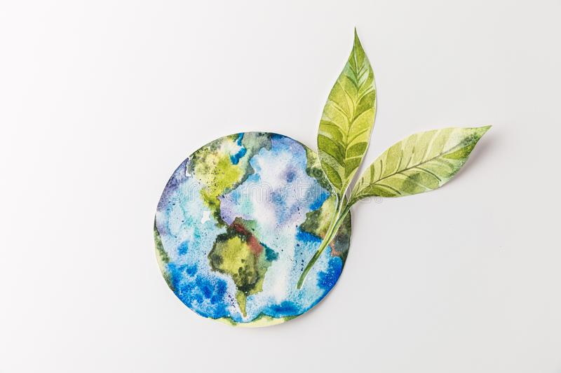 top view of handmade colorful paper globe with green leaves isolated on grey, environment protection and recycling concept royalty free stock photo