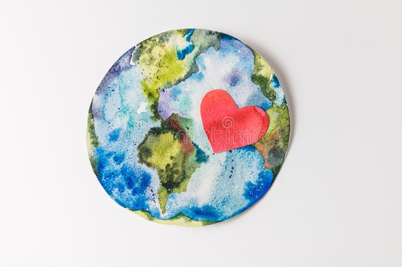 Top view of handmade colorful paper globe with red heart isolated on grey, environment protection and recycling concept stock images