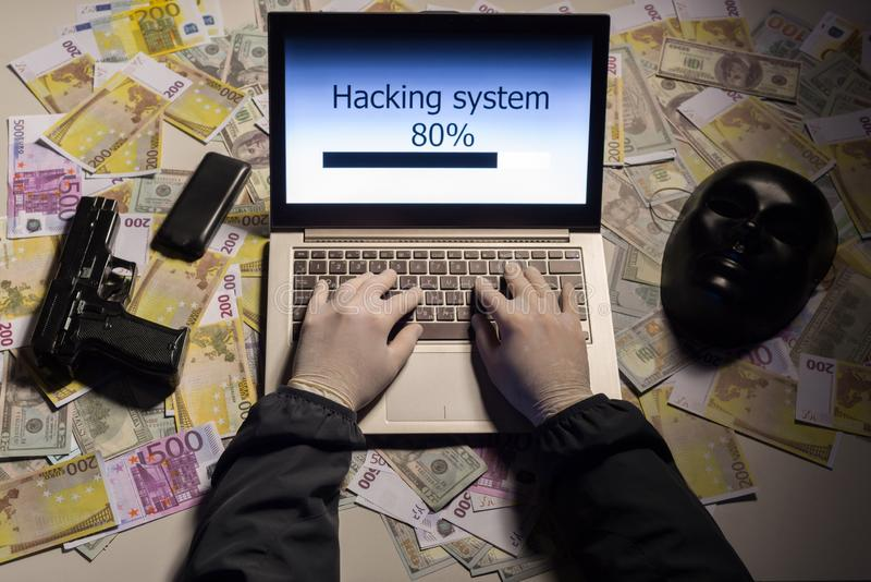 Top view on the hands of an attacker programmer hacking a data server from his laptop. Money is thrown on the table, lies a. Telephone, a gun, and a mask. The royalty free stock images