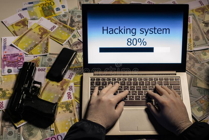 Top view on the hands of an attacker programmer hacking a data server from his laptop. Money is thrown on the table, lies a. Telephone, a gun, . The concept of stock images