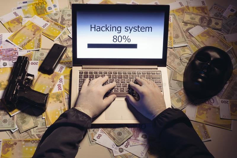Top view on the hands of an attacker programmer hacking a data server from his laptop. Money is thrown on the table, lies a. Telephone, a gun, and a mask. The stock image
