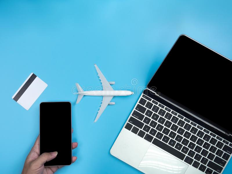 Top view of hands with smartphone , laptop, credit card and plane on blue isolated background with copy space. stock photos
