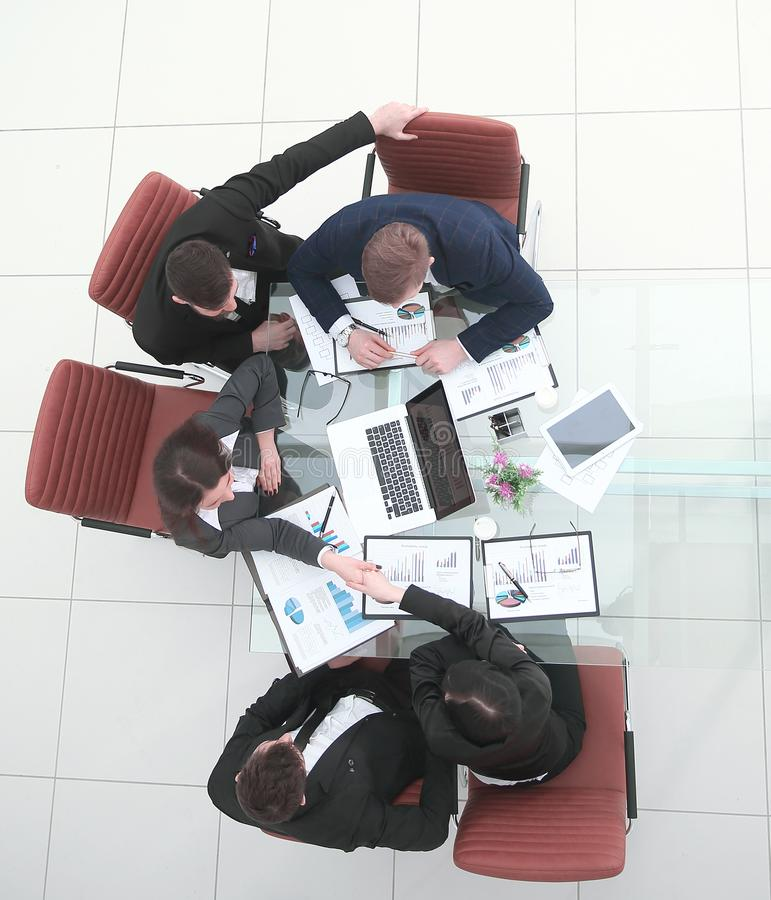 Top view.handshake of colleagues after discussing a new financial project.  royalty free stock image