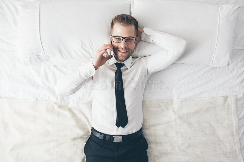 Top view. Handsome businessman with glasses on bed calling from his phone royalty free stock photography