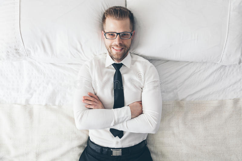 Top view. Handsome businessman with glasses lying on bed stock image