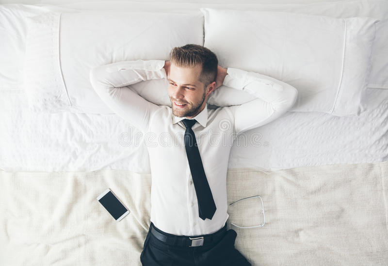 Top view. Handsome businessman relaxing on bed after a tough day at work stock image