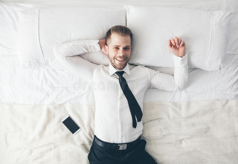 Top view. Handsome businessman relaxing on bed after a tough day at work stock photography