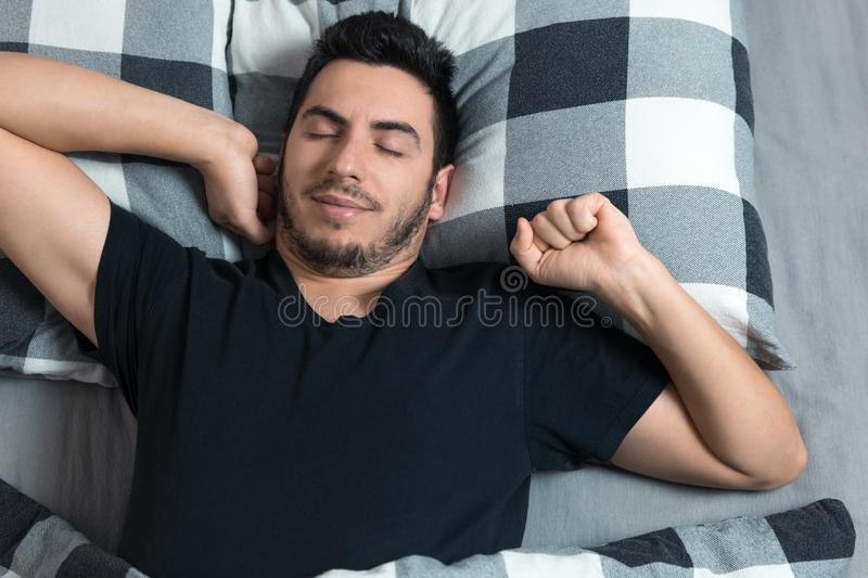 Top view of handsome man yawns and rubs his eyes while sleeping. In bed royalty free stock photos