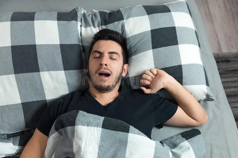 Top view of handsome man yawns and rubs his eyes while sleeping. In bed stock image
