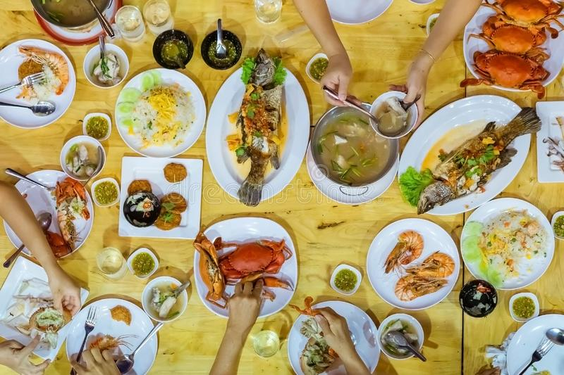 Top view of Happiness family enjoy eating with a variety of seafood dishes royalty free stock photo