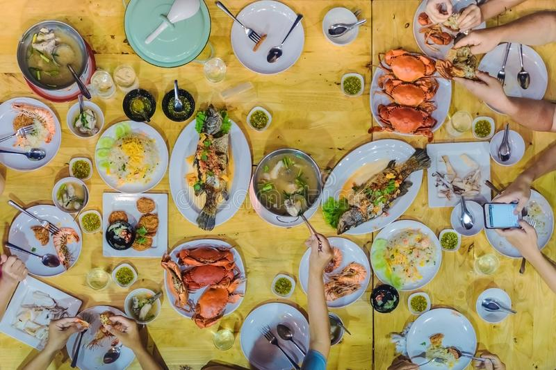 Top view of Happiness family enjoy eating with a variety of seafood dishes stock photography