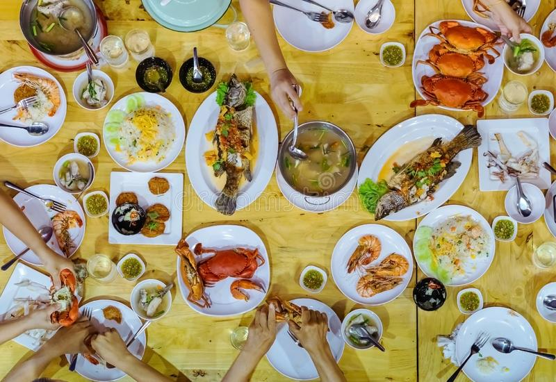 Top view of Happiness family enjoy eating with a variety of seafood dishes stock photo