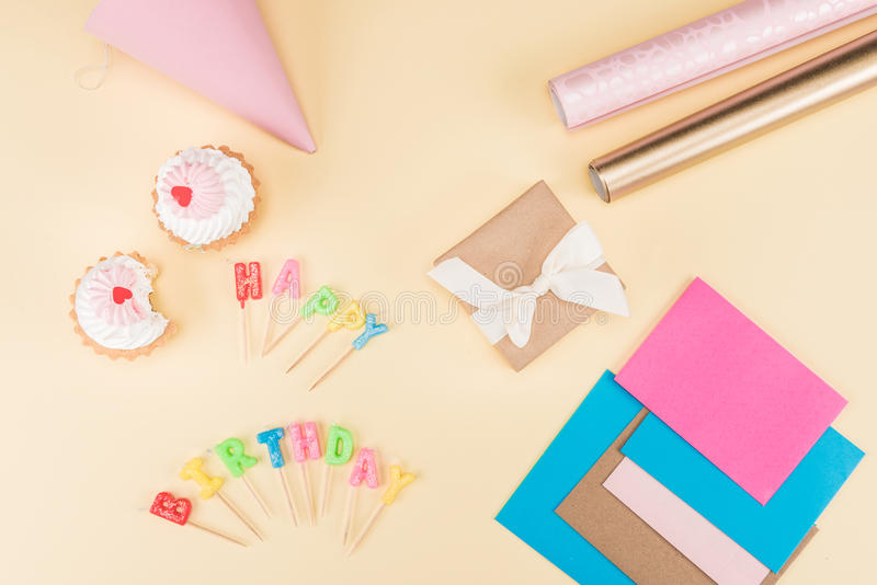 Top view of happy birthday lettering, envelope with ribbon, cakes and colorful cards on pink. Birthday party concept stock photo