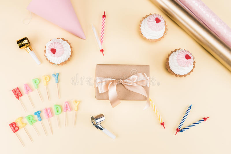 Top view of happy birthday lettering, envelope with ribbon, cakes and colorful cards on pink. Birthday party concept stock image