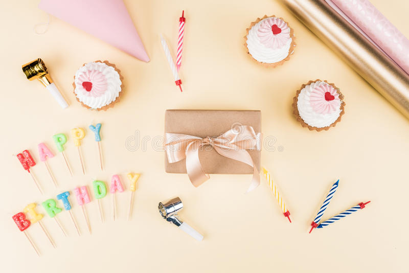 Top view of happy birthday lettering, envelope with ribbon, cakes and colorful cards on pink. Birthday party concept stock photos