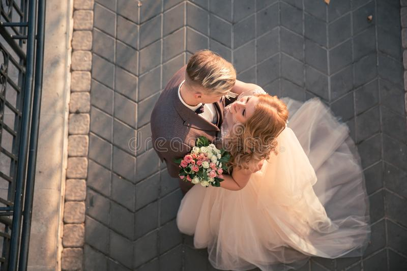 Top view. happy bride and groom standing on the stone pavement royalty free stock images