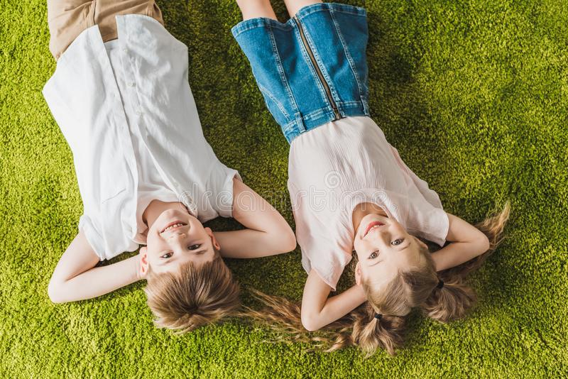 Top view of happy children lying on lawn and smiling. At camera stock photos