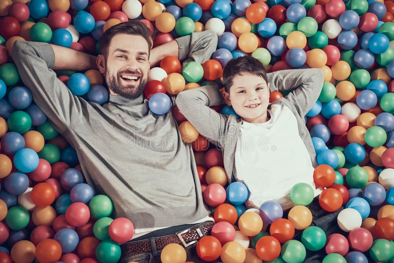 Top view. Happy dad and son in pool with balls royalty free stock photos