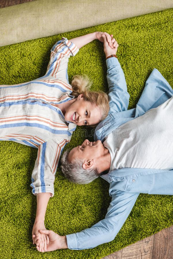 top view of happy elderly couple lying together on carpet and holding hands royalty free stock photos