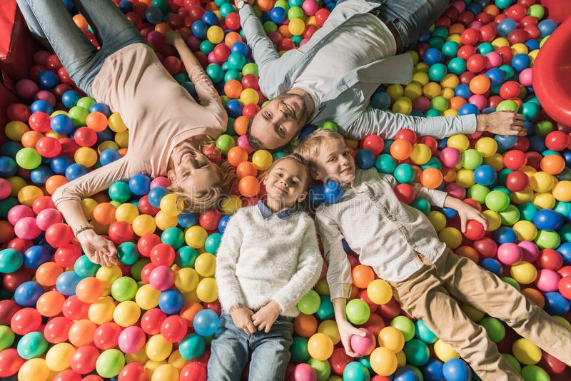 top view of happy family with two kids smiling at camera while lying in pool with colorful balls stock images