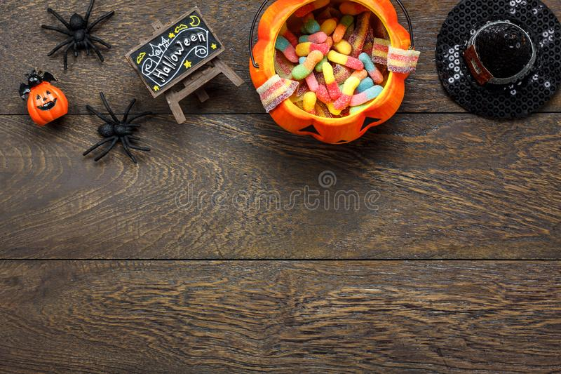 Top view of Happy Halloween decorations festival and candy trick or treat background. All accessory on modern rustic brown wooden at home office desk.Free space royalty free stock image