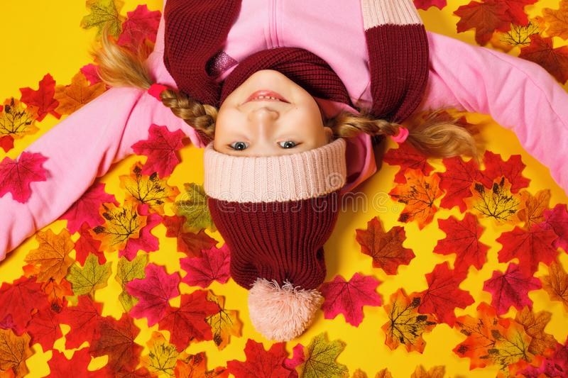 Top view of a happy little girl lying on autumn leaves. The child is upside down in a scarf and hat royalty free stock image
