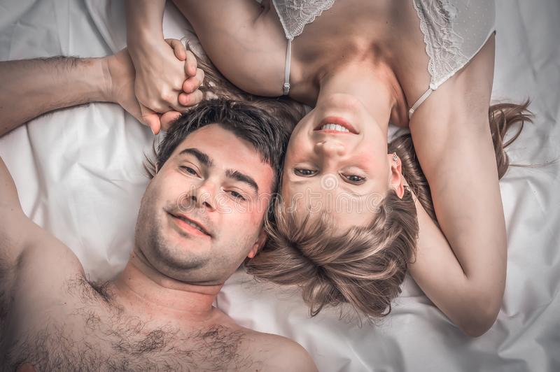 Top view of loving couple lying together in bed stock images