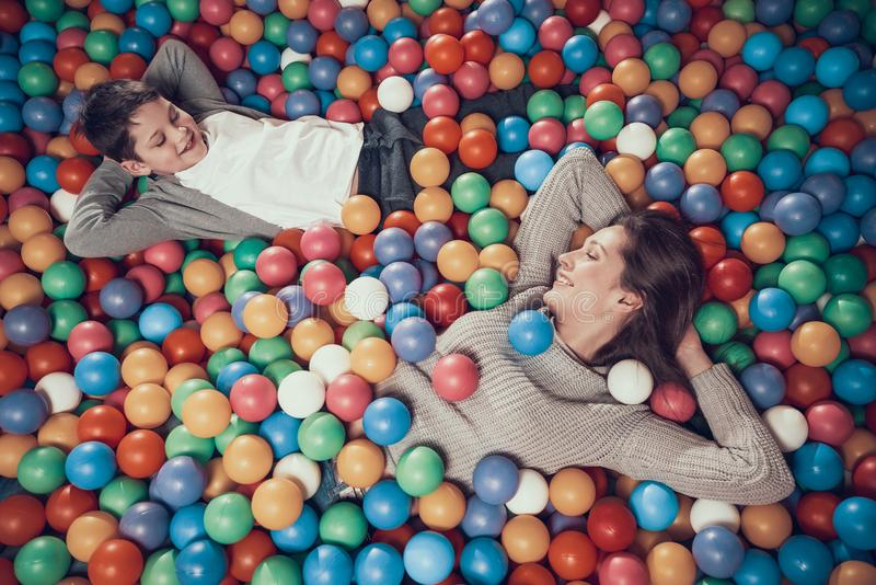 Top view. Happy mom and son in pool with balls royalty free stock photos