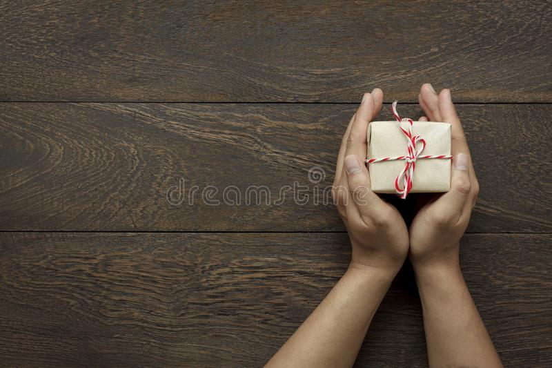 Top view Happy new year festival or Birthday and Merry Christmas day background concept. Hands holding the little present.Object on the modern brown rustic wood royalty free stock images