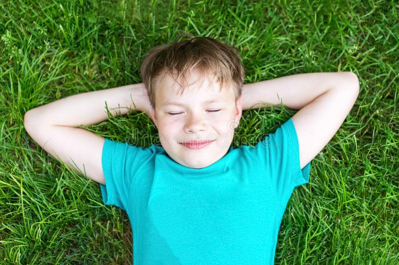 Top view of a happy smiling caucasian boy relaxing on the grass royalty free stock photo