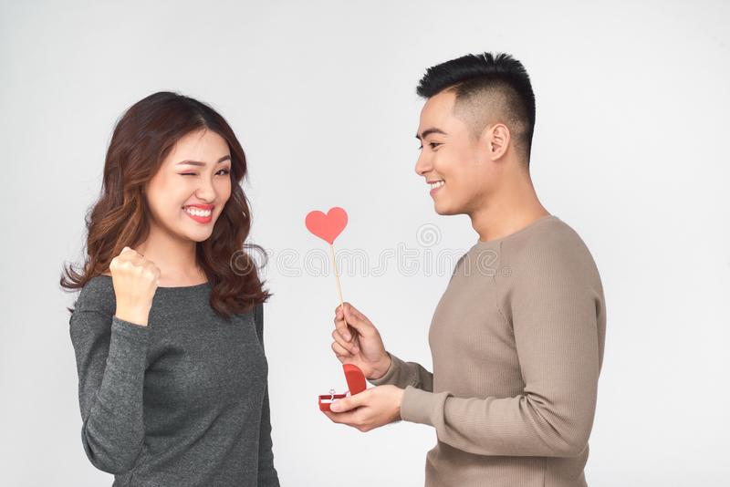 Top view of happy young couple looking at each other and smiling . Girl is holding a red paper heart stock photo