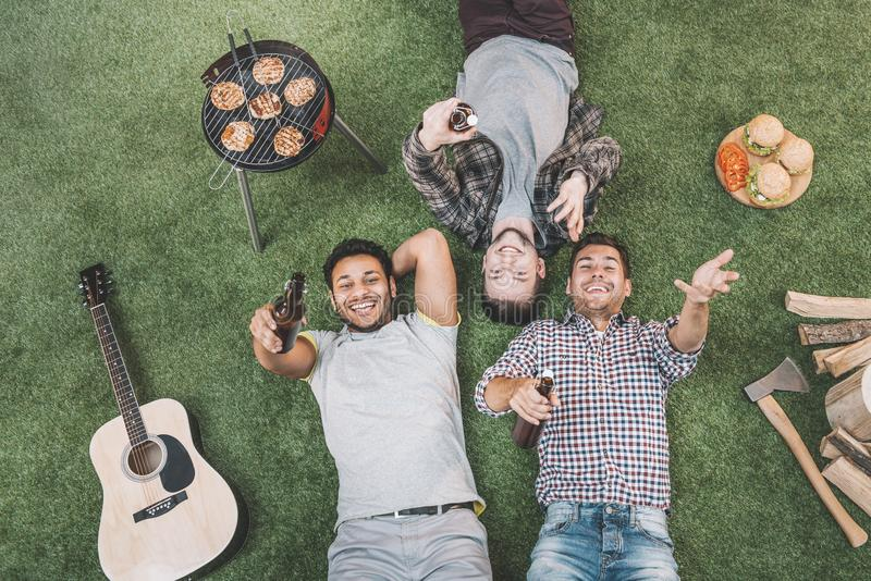 Top view of happy young men lying on grass with beer bottles while grilling meat royalty free stock image