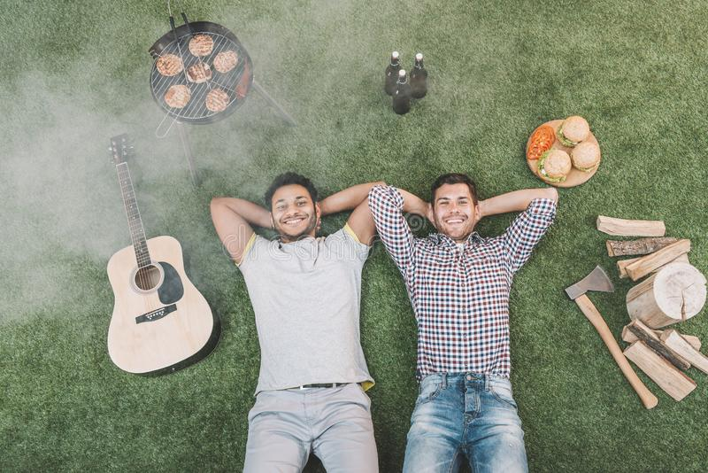 Top view of happy young men resting on grass with guitar and food for picnic stock photography