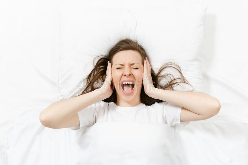 Top view of head of tired brunette young woman lying in bed with white sheet, pillow, blanket. Shocked female cover ears royalty free stock photo