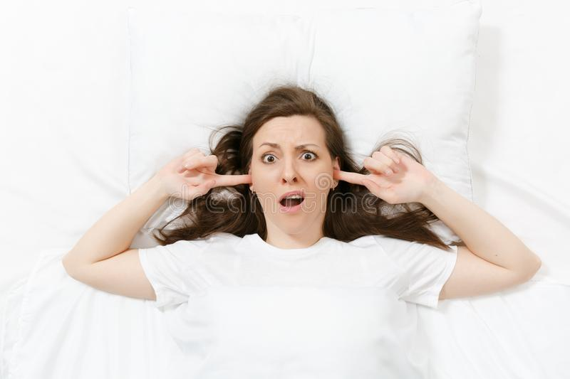 Top view of head of tired brunette young woman lying in bed with white sheet, pillow, blanket. Shocked female cover ears stock photos