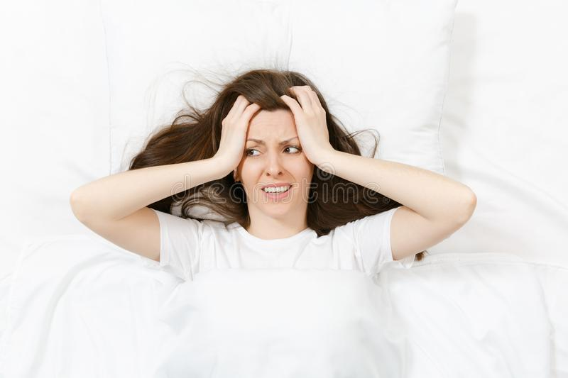 Top view of head of tired brunette young woman lying in bed with white sheet, pillow, blanket. Shocked female cover ears stock photography