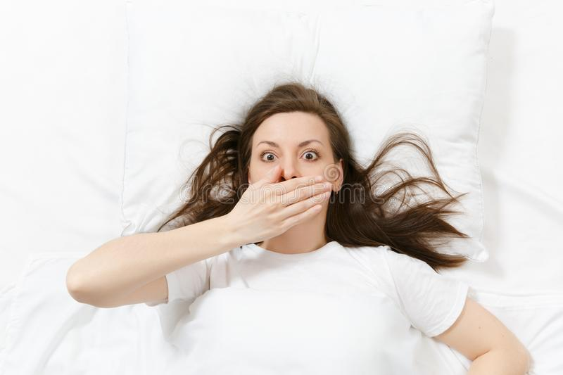 Top view of head of tired brunette young woman lying in bed with white sheet, pillow, blanket. Shocked female cover stock image