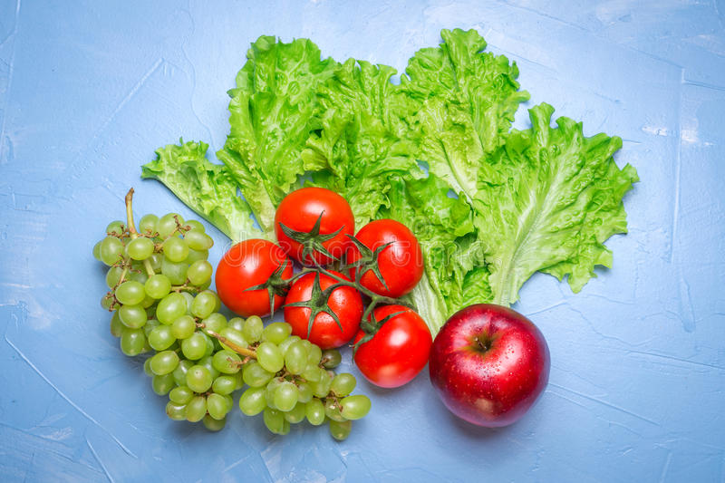 Top view of health food: tomato, apple, grape, salad. Healthy ea stock images
