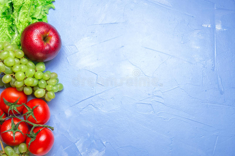 Top view of health food: tomato, apple, grape, salad. Healthy ea royalty free stock images