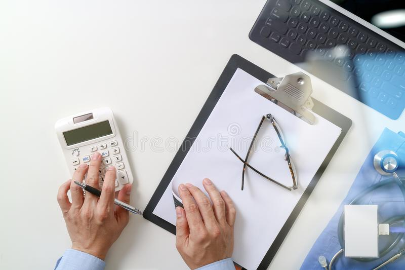 Top view of Healthcare costs and fees concept.Hand of smart doctor used a calculator for medical costs in modern hospital royalty free stock photography