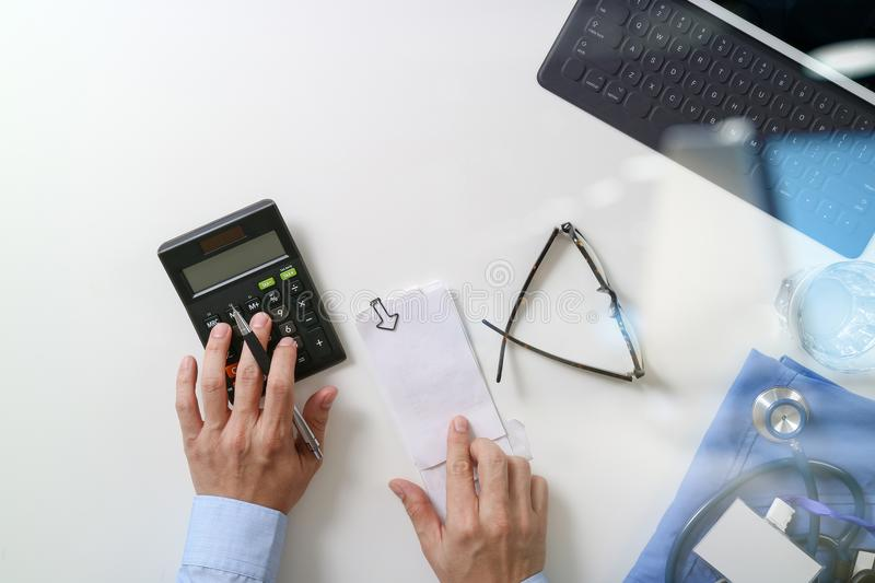 Top view of Healthcare costs and fees concept.Hand of smart doctor used a calculator for medical costs in modern hospital royalty free stock photos