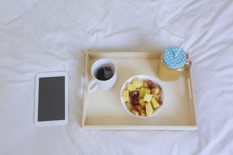 top view of a healthy breakfast on bed. Coffee, orange juice and fruit. Tablet besides. Home, indoors and lifestyle stock photography