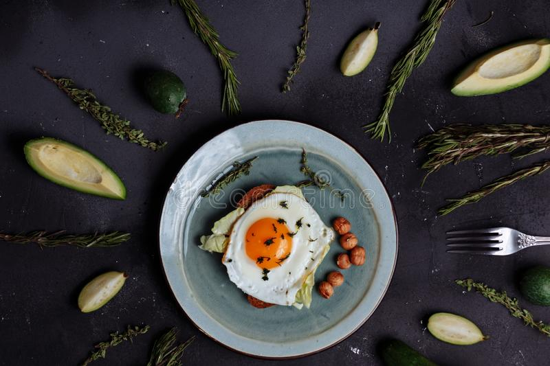 Top view of healthy breakfast scrambled eggs with bread and nuts in a plate on black background with avocado, rosemary royalty free stock photos