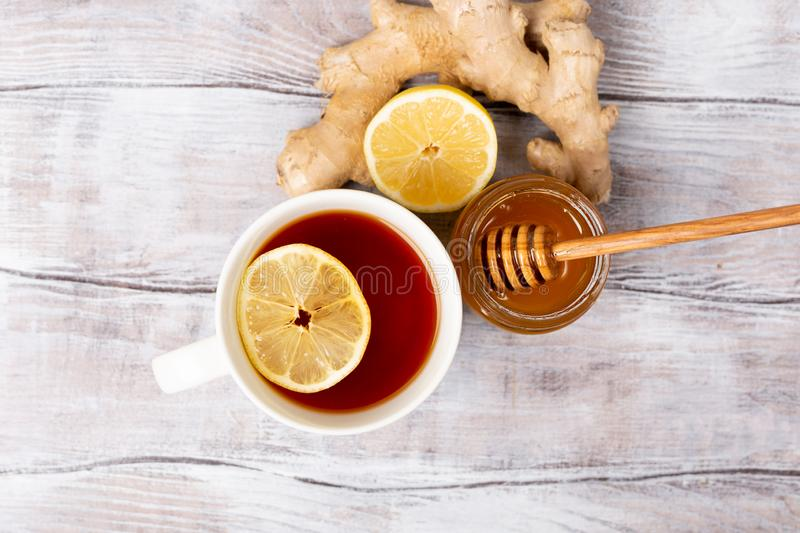 Top view. Healthy concept. Tea, lemon, ginger, honey on a white wooden background. Flat lay. Treatment of cold and. Viruses. Be healthy stock photography
