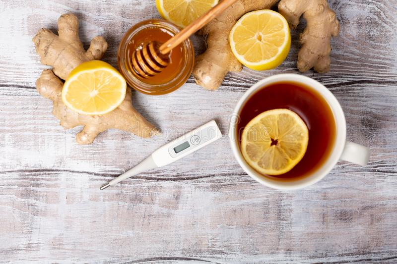 Top view. Healthy concept. Tea, lemon, ginger,thermometer, honey on a white wooden background. Flat lay. Treatment of. Cold and viruses. Be healthy royalty free stock photos