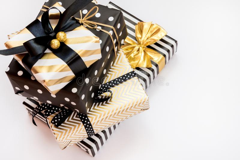 Top view of a heap of gift boxes in various black, white and golden designs. A concept of Christmas, New Year, birthday celebratio royalty free stock image